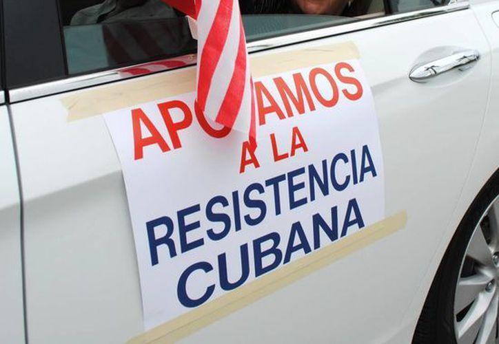 Una mujer saluda desde su auto a su llegada a la concentración de unos 300 exiliados cubanos en Miami, Florida, para exigir al presidente Barack Obama que no retome las relaciones diplomáticas con Cuba sino hasta que exista libertad en el país. (EFE)