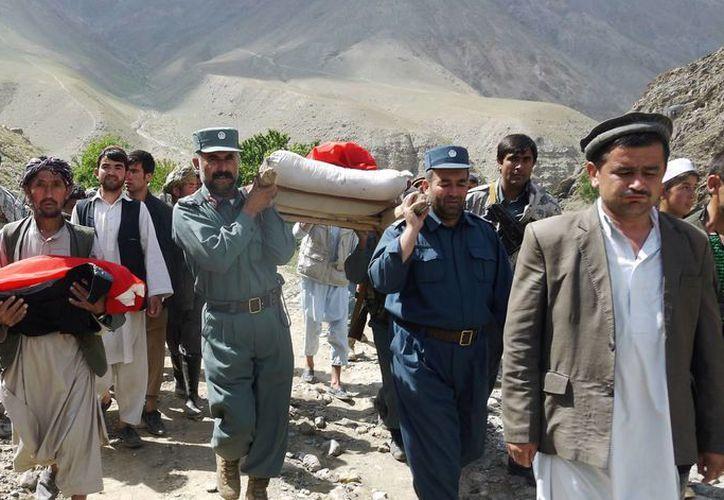 La policía y los aldeanos afganos trasladan los cuerpos de las víctimas. (Agencias)