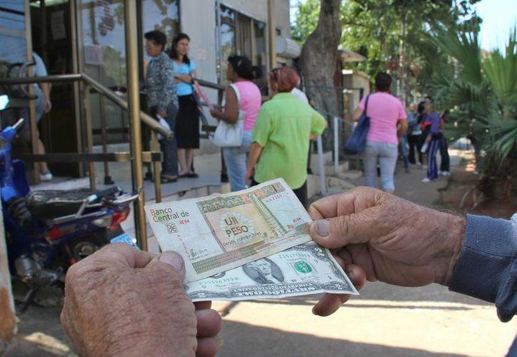 Un hombre muestra un peso convertible cubano y un dólar estadounidense frente a una oficina de la Western Union en La Habana, Cuba. (Archivo/EFE)