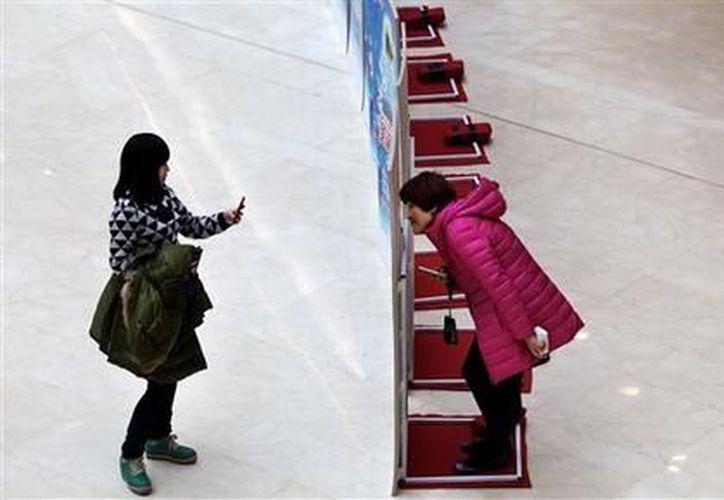 Una mujer usa su teléfono móvil para fotografiar a otra en Beijing.  (Agencias)
