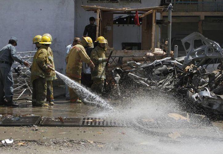 Bomberos apagan un incendio tras el atentado en la zona del Nuevo Banco de Kabul. (Agencias)