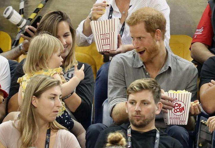 Harry miró a la niña y sonriendo le compartió un poco de su comida. (Hola)