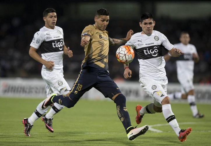 Pumas llegó a 12 unidades para asegurar el pase a la siguiente ronda como líder de grupo. En la foto, Ismael Sosa(pumas) realiza un disparo hacia portería ante la mirada de su oponente.(AP)