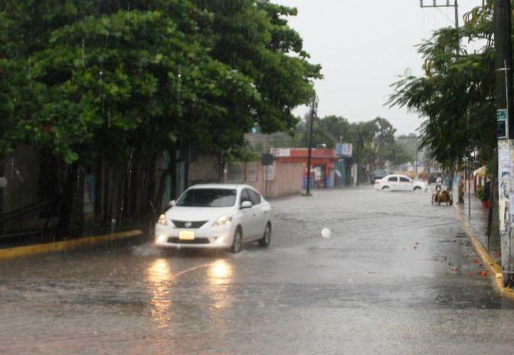 Se dificulta el andar de los habitantes y turistas debido a los baches que origina la lluvia en Tulum. (Rossy López/SIPSE)