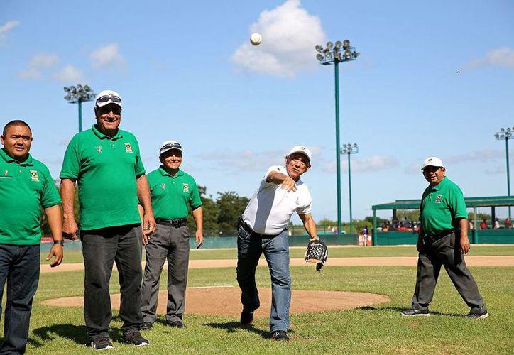 Juan Sosa Puerdo, director del IDEY, al momento de lanzar la primera bola previo al arranque de los juegos. (Milenio Novedades)