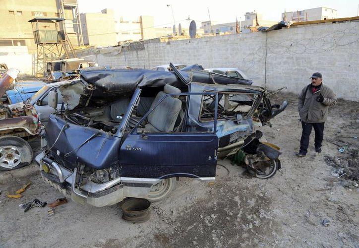 Inspectores revisan la zona de uno de los atentados con coche bomba cometidos en los alrededores de Bagdad. (Agencias)