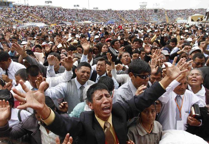 Cientos de personas oran en el Congreso Nacional del Movimiento Misionero en en el Estadio San Marco en Lima. (Agencias)