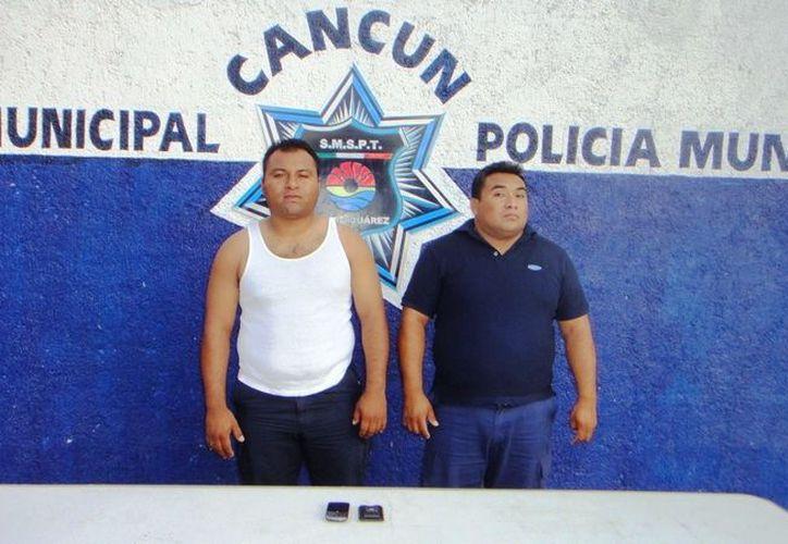 Los agentes Luis Ángel Gómez Cox y José Alejandro García Magaña, fueron acusados de robar a una persona en una parada de combis en Puerto Morelos. (Redacción/SIPSE)