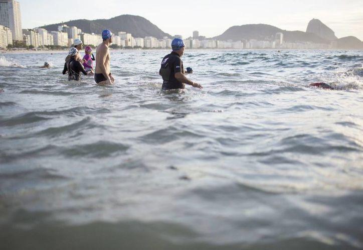 Un grupo de personas entra al agua en la playa de Copacabana en Río de Janeiro, Brasil. (AP Photo/Leo Correa)