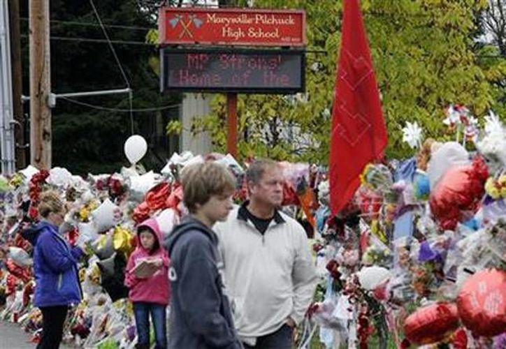 Desde la izquierda: Gay Soriano, su hija Gabby, de 11 años, su hijo Titan, 13, y su esposo Rick, visitan el jueves 30 de octubre de 2014 el monumento improvisado en recuerdo de las víctimas de la balacera fatal ocurrida hace casi una semana en una escuela de Marysville, Washington. (Agencias)