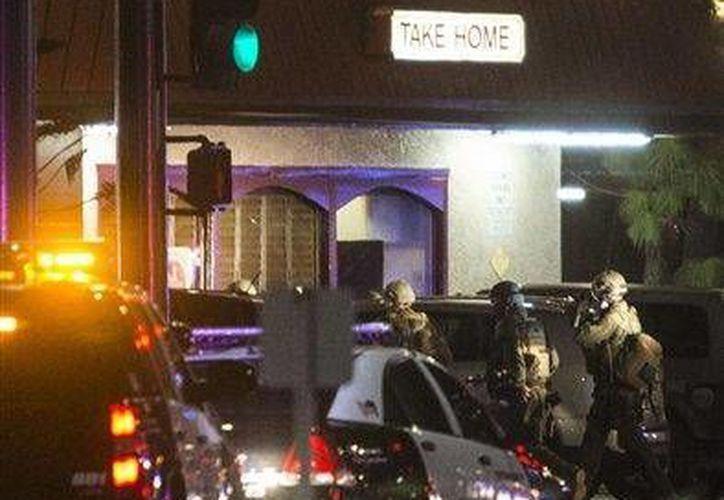 Agentes de SWAT del departamento del alguacil de Los Angeles entran al restaurante Chris' and Pitt's luego de que un hombre armado irrumpiera al lugar y tomara cuatro rehenes. (Agencias)