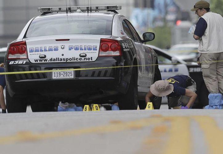 Los investigadores trabajan en el área del centro de Dallas, donde cinco agentes perdieron la vida en un tiroteo. (Agencias)