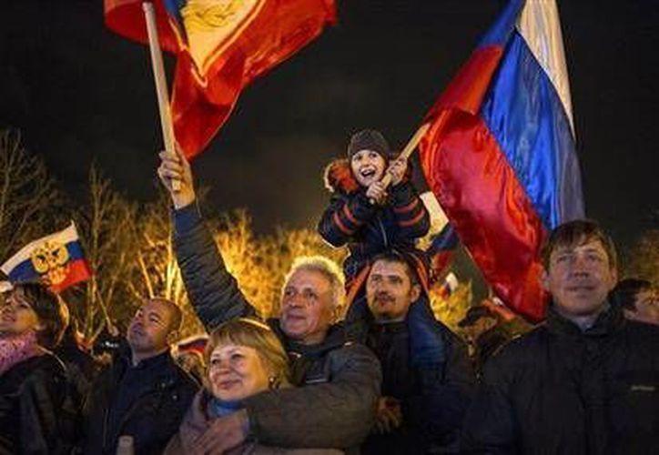 Manifestantes prorrusos celebran en la plaza de Sebastopol, Ucrania, los resultados del referéndum que decidió la separación de la península de Crimea de esta nación el lunes 17 de marzo de 2014. (Foto de AP/Andrew Lubimov)