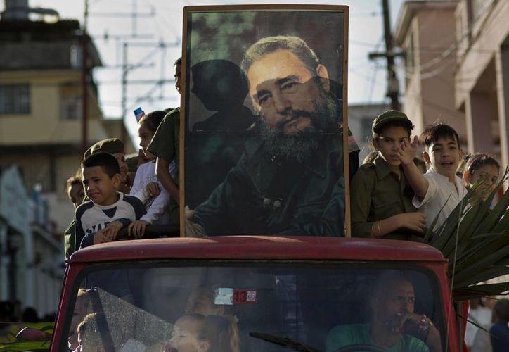 Niños muestran la imagen de Fidel Castro durante la celebración del 56 aniversario en que el expresidente entró a Cuba. (Agencias)