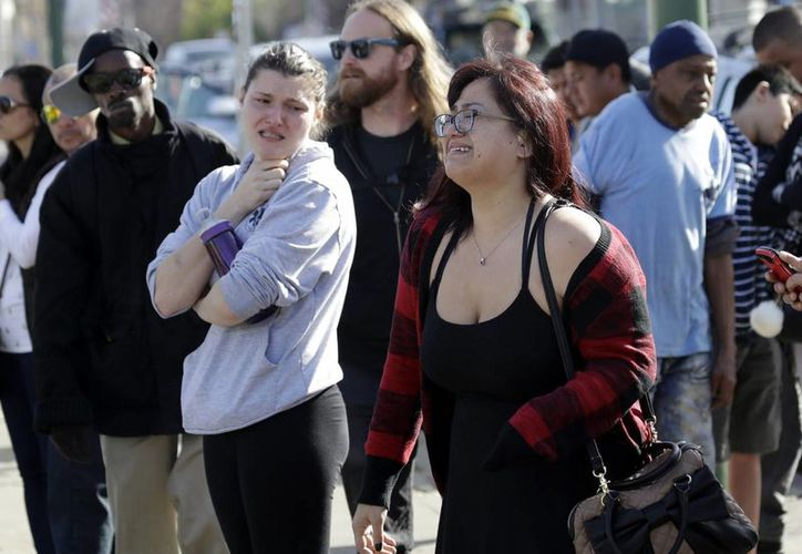 Dos mujeres lloran afuera de un almacén en Oakland, California, tras el incendio ocurrido el viernes en el lugar donde se efectuaba una fiesta. (AP/Marcio Jose Sanchez)