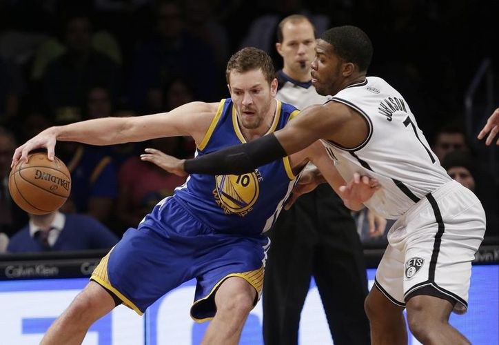 Joe Johnson, de Nets (d), defiende ante David Lee (10), de Golden State, en el duelo de temporada regular de la NBA. (Agencias)