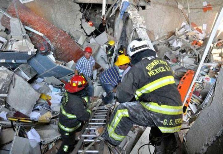 Integrantes del cuerpo de bomberos trabajan en el rescate de los trabajadores que pudieran estar atrapados. (Foto: Milenio)