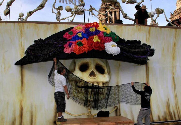 Artistas decoran una tradicional Catrina mexicana como parte de los festejos del Día de Muertos en el Zócalo de la Ciudad de México. (Agencias)