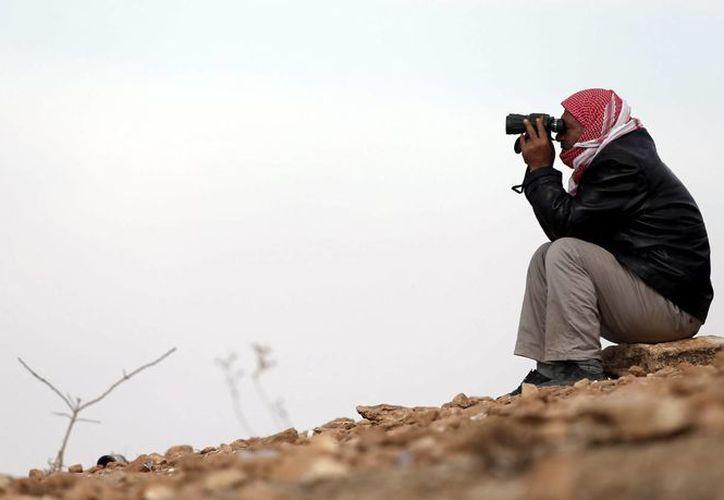 Un hombre observa con sus prismáticos desde territorio turco los combates entre los kurdos sirios y milicianos del Estado Islámico en la localidad siria de Kobani, cerca del distrito de Suruc, Turquía. (EFE)