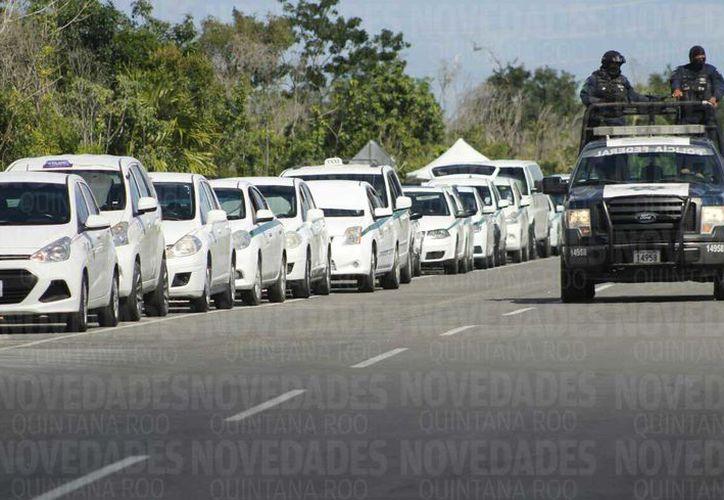 Los conductores se encuentran estacionados sobre la carretera con dirección al Aeropuerto de Cancún. (Jesús Tijerina/ SIPSE)