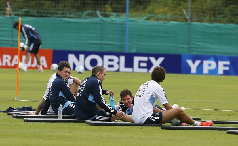 Maxi Rodríguez (i), Rodrigo Palacio (2-i) y Lionel Messi (2-d) descansan de un entrenamiento. (EFE)