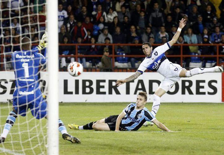 El jugador de Huachipato Braian Rodríguez (d) patea el balón ante Gremio este 18 de abril, durante el partido de vuelta de la primera fase de la Copa Libertadores. (EFE)