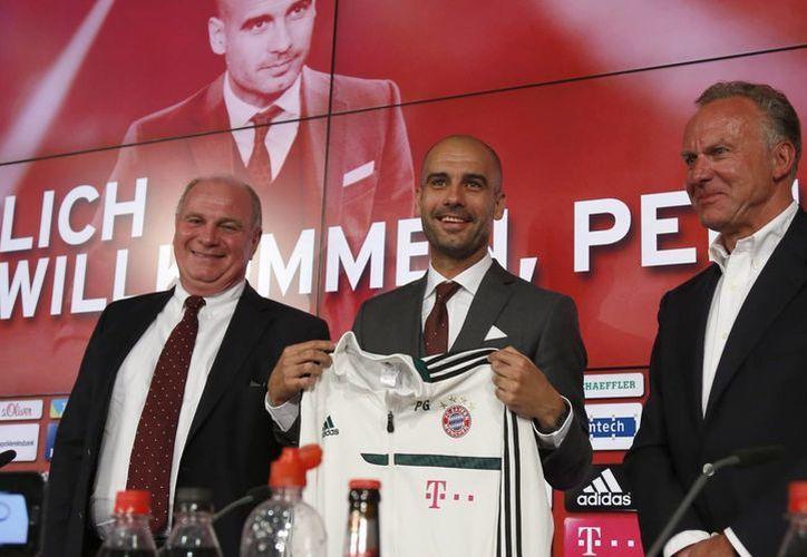 Guardiola durante su primera conferencia como entrenador del Bayern, flanqueado por Rummenigge (d) y el presidente del club, Uli Hoeness. (Agencias)