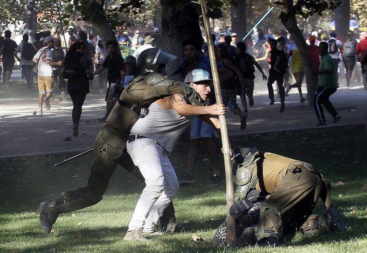 Un manifestante es detenido por policías en Chile, donde miles de personas exigen una nueva constitución y educación gratuita y de calidad. (Agencias)