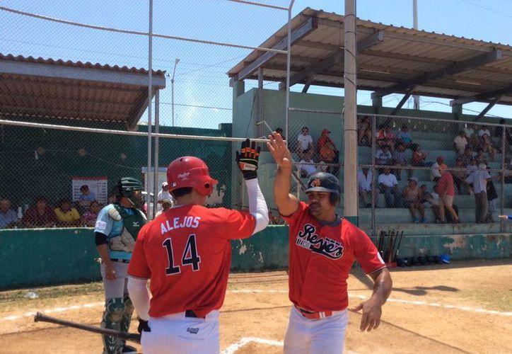 En la foto, Fernado Alejos felicita a su compañero tras anotar una de las carreras del equipo Reyes de Tizimín. (Milenio Novedades)