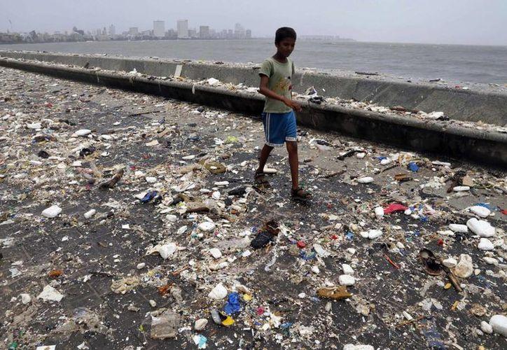 Un chico camina entre todo tipo de basura que dejó la marea en Mumbai, India, el 12 de junio de 2014. (Agencias)