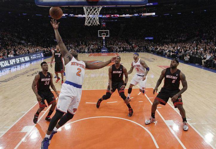 Raymond Felton (2), de Knicks, encesta mientras lo observan Norris Cole (30), Chris Bosh (1) y LeBron James (6) del Heat de Miami. (Agencias)