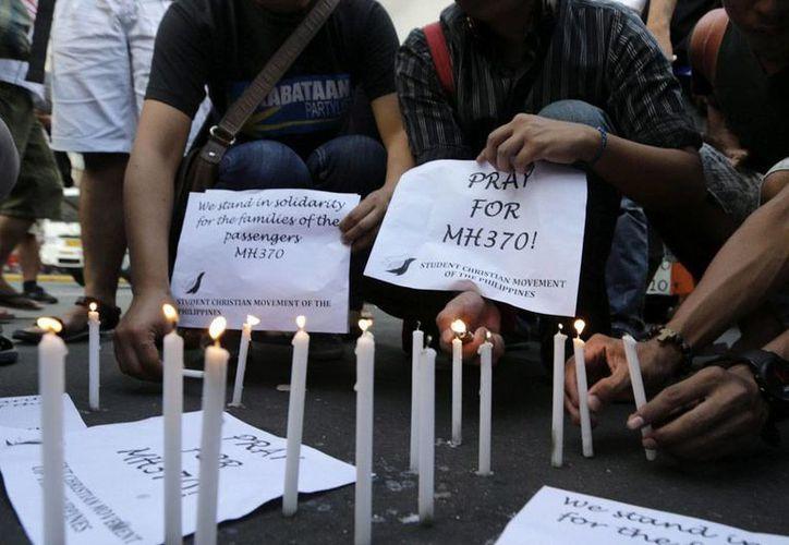 Ni las autoridades de Malasia, ni el FBI descartan que los pasajeros del avión desaparecido estén vivos. En la imagen, estudiantes filipinos encienden velas durante una jornada de rezos por los tripulantes del avión de Malaysia Airlines que con 239 personas a bordo desapareció el 8 de marzo, en Manila (Filipinas). EFE