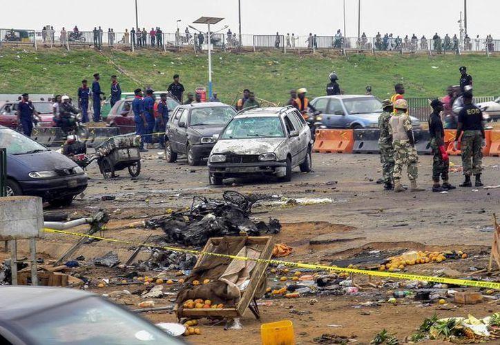 Oficiales de la policía nigeriana observan el lugar donde un coche bomba explotó en Nyana, Abuya, en fechas recientes. (EFE/Archivo)