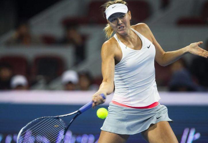 La tenista rusa María Sharapova, que jugará en México por primera vez, devuelve la pelota a Carla Suárez en el Abierto de Pekín. (EFE)