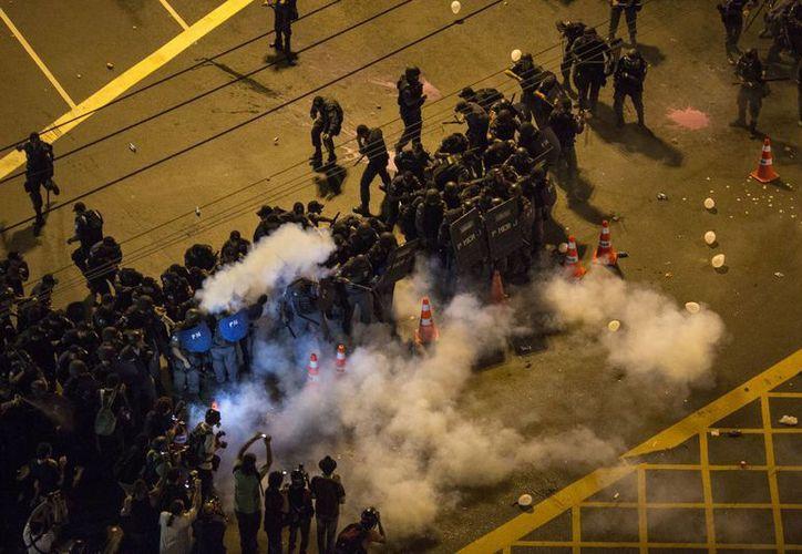 La policía durante un enfrentamiento con manifestantes al exterior del estadio Maracaná en Río de Janeiro. (Agencias)