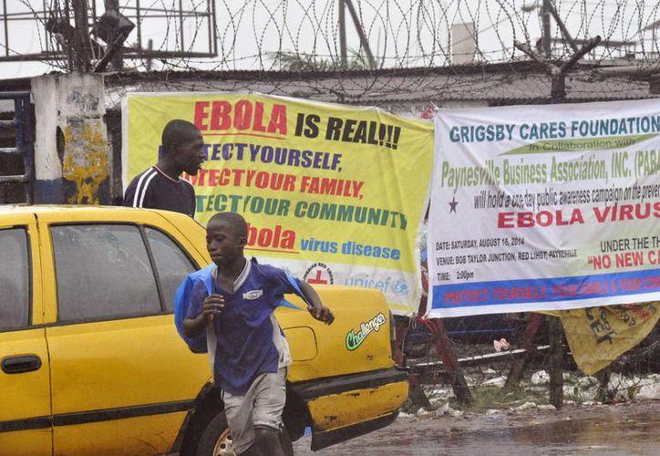 Dos personas pasan junto a letreros que advierten de los riesgos del virus del ébola, en la ciudad de Monrovia, Liberia, este domingo. (Foto AP/Abbas Dulleh)