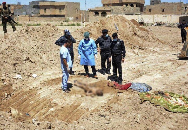 Un equipo forense de las fuerzas de seguridad iraquíes trabaja en el sitio de una fosa común que se cree contiene los cuerpos de civiles iraquíes, fuerzas de seguridad y miembros de sus familias, muertos por el Estado Islámico. (AP)