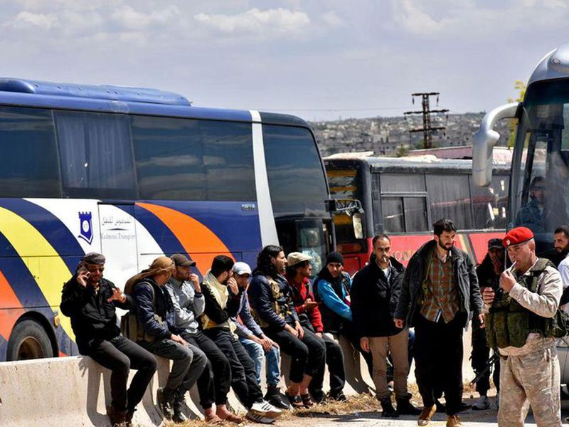 Syrian government forces oversee the evacuation by buses of opposition fighters and civilians.