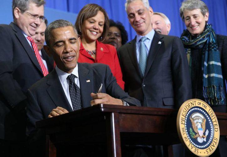 El presidente Barack Obama firma la ley de proclamación dedicada al Monumento Nacional Pullman, en el Colegio Gwendolyn Brooks, en Chicago, illinois, este jueves 19 de febrero de 2015. (AP)