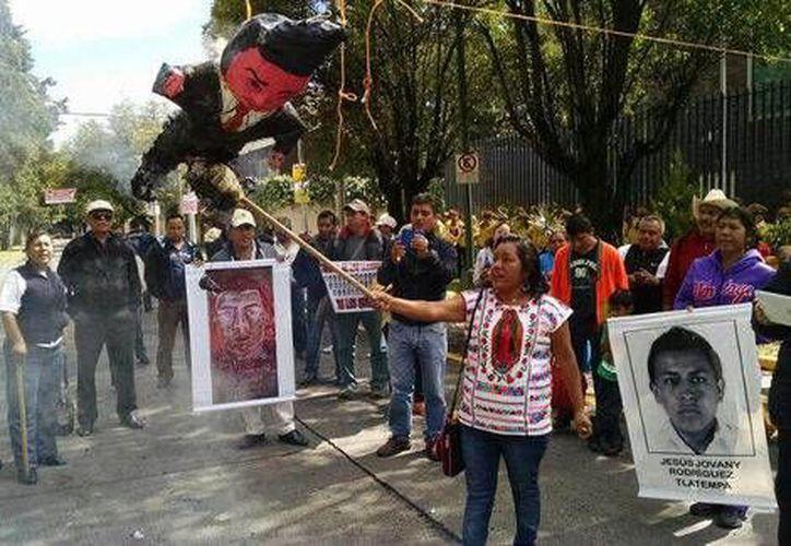 Los manifestantes golpearon y quemaron frente a la embajada de Alemania tres piñatas que representaban al exgobernador de Guerrero, Ángel Aguirre, al alcalde de Cocula y al presidente Enrique Peña Nieto. (Fotos de Milenio)
