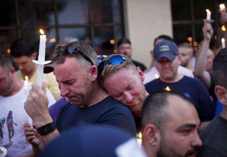Paul Cox (der), se apoya en el hombro de Brian Sullivan, durante una vigilia por la muerte a tiros de varias personas en un club nocturno de Orlando. (Agencias)