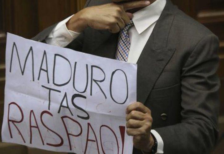 """El legislador de oposición Luis Silva muestra un cartel hacia la bancada oficialista que dice """"Maduro tas raspao"""" (en jerga estudiantil: """"Maduro estás reprobado"""") durante la sesión en que los opositores aprobaron en la Asamblea Nacional una declaratoria de abandono del cargo del presidente Nicolás Maduro, en Caracas, Venezuela.(AP/Fernando Llano)"""