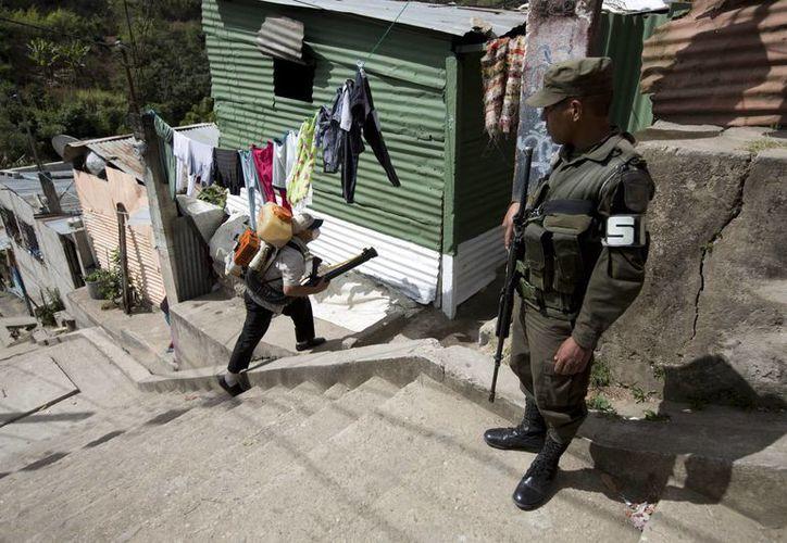 Un soldado proporciona seguridad a un trabajador del Ministerio de Salud que fumiga contra el mosquito Aedes aegypti en La Comuna 2, un vecindario de Ciudad de Guatemala. (Agencias)