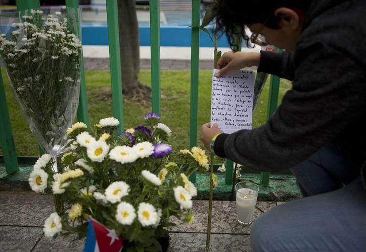 Una mujer deja flores en señal de respeto afuera de la embajada de Cuba en la Ciudad de México. (AP/ Rebecca Blackwell)