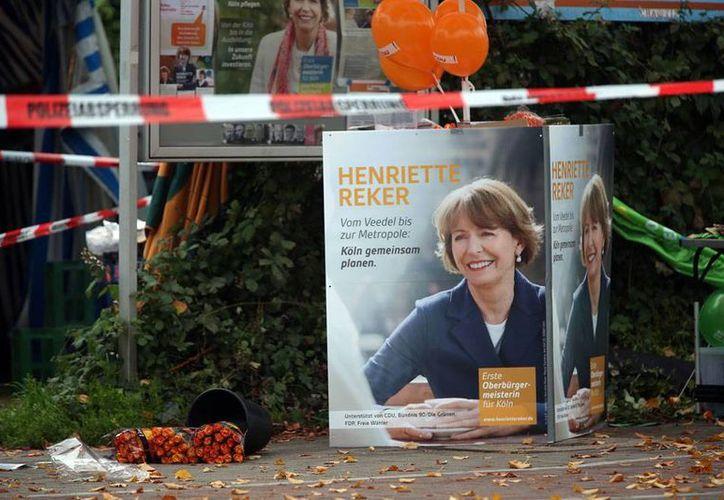 Un cartel con la imagen de la candidata Henriette Reker aparece cerca del lugar donde fue herida con un arma blanca. Su vida, según las autoridades, corre peligro. (AP)