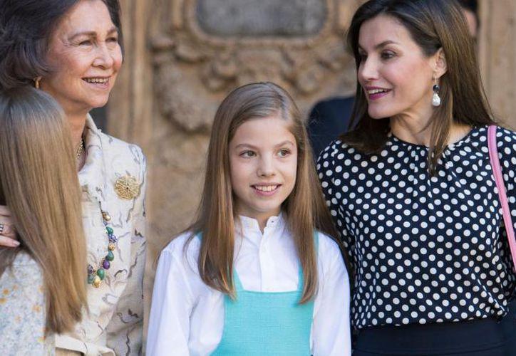 Momento en que la reina Sofía intenta tomarse una foto con sus nietas y es abordada por la reina Letizia para impedirlo. (Foto: AFP)