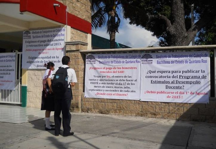 Los maestros colgaron mantas en las que demandan el pago del SAR. (Tomás Álvarez/SIPSE)