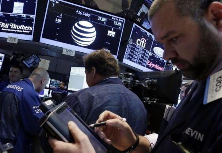 Operadores alrededor de la mesa que maneja las acciones de AT&T en el piso de la Bolsa de Valores de Nueva York. (Agencias)