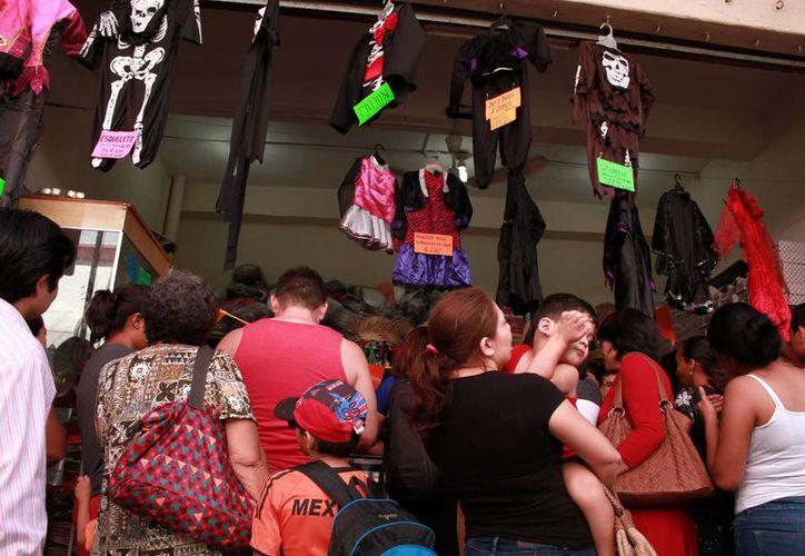 Las tiendas de venta de disfraces registraron buenas ventas desde la semana pasada. Imagen de un grupo de clientes en un comercio del centro de Mérida. (Milenio Novedades)