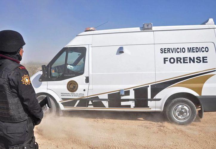 Un policía hace guardia ante la camioneta del Semefo que llevó los cuerpos al anfiteatro. (Agencias)